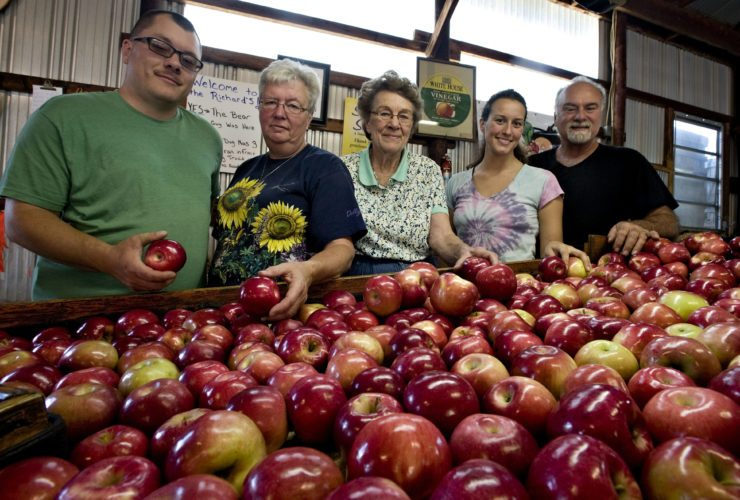 Cameron Richard, from left, Debbie Fauble, Mary Richard, Kayla Lawrence and Eddie Richard stand behind a bin of Ida red apples at Richard's Fruit Market in Middletown. The business is celebrating 61 years of operation. Rich Cooley/Daily